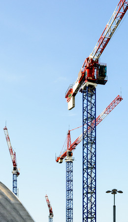 Four tower cranes on a construction site in the middle of a business district in full development.