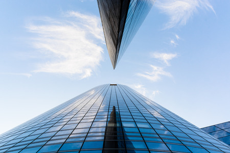 Low angle view of skyscrapers and glass buildings with blue sky in a geometric arrangement.