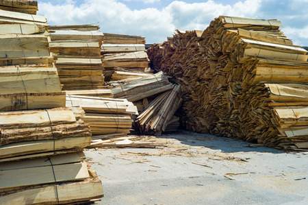 Several piles of rough timber boards stacked on the ground under the sun in front of a sawmill.