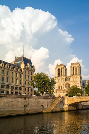 Notre-Dame cathedral in Paris and the Police headquarters under a warm sunlight with the river Seine in the foreground.
