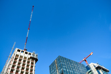 Low angle view of two concrete buildings under construction with tower cranes at their tops next to a glass building against blue sky.