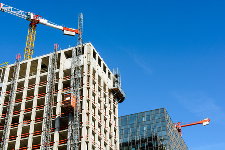 Low angle view of a concrete building under construction next to a glass building with two tower cranes against blue sky.