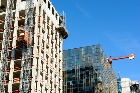 Low angle view of a glass building between two concrete buildings under construction with a red tower crane against blue sky.