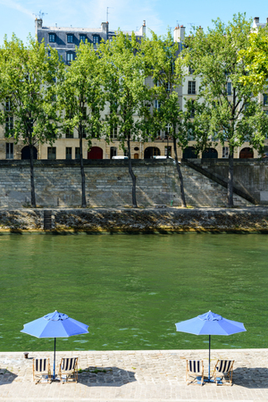 poplar  banks: Two blue parasols with blue and white striped deck chairs in the sun on the bank of the river Seine with poplar trees and typical parisian buildings in the background.