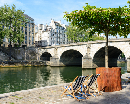 poplar  banks: Two blue and white striped deck chairs in the sun on the bank of the river Seine with typical parisian bridge and buildings in the background.
