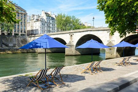 poplar  banks: Three blue parasols with blue and white striped deck chairs in the sun on the bank of the river Seine with typical parisian bridge and buildings in the background.