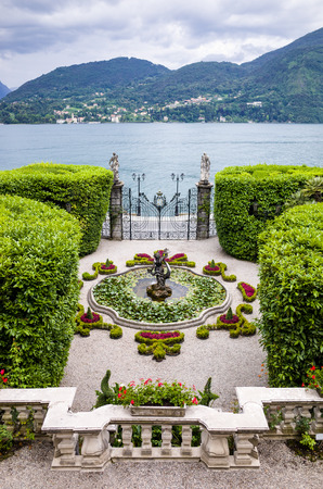 Como, Italy - June 15, 2014: View from balcony of an italian villas garden right on Lake Como with balcony, fountain, gate and statues.