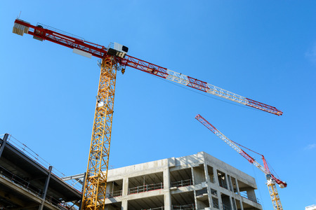 Low angle view of two tower cranes with a concrete building under construction with blue sky.