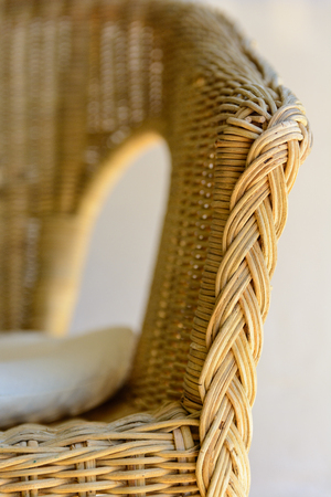 vintage furniture: A rattan armchair with a white cushion. Stock Photo