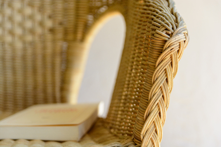 A rattan armchair with a book.