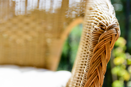 A rattan chair with a white cushion in the sunlight on a balcony with planter.