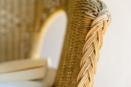 vintage furniture: A rattan armchair with a white cushion and a book.