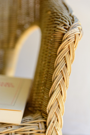 vintage furniture: A rattan armchair with a book.