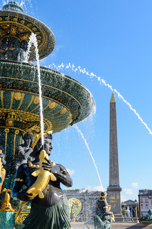 The Fountain of the Seas, on the Concorde place in Paris, and the obelisk of Luxor in the background, with Nereids and Tritons holding golden fishes spouting water upwards to the vasque. Stock Photo