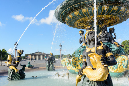 The Fountain of the Seas, on the Concorde place in Paris, and the Bourbon Palace in the background, with Nereids and Tritons holding golden fishes spouting water upwards to the vasque. Stock Photo