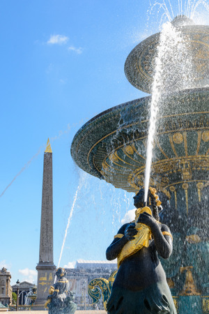 The Fountain of the Seas, on the Concorde place in Paris, and the obelisk of Louxor in the background, with Nereids and Tritons holding golden fishes spouting water upwards to the vasque.