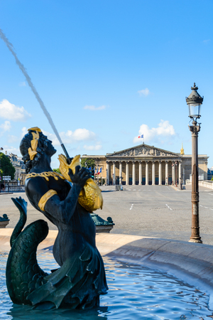 The Fountain of the Seas, on the Concorde place in Paris, and the Bourbon Palace in the background, with Nereids and Tritons holding golden fishes spouting water upwards. Stock Photo