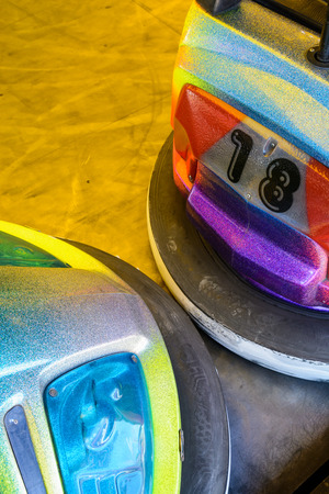 Close-up view of the front and rear parts of two colorful dodgem cars in a funfair.