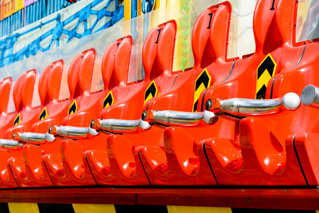 Row of empty vivid red seats of a thrilling ride in a funfair.