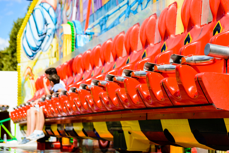 Row of vivid red seats of a thrill ride in a funfair, with teenagers waiting for the start. Stock Photo