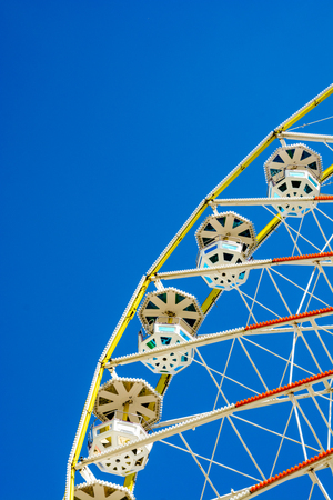 A Ferris wheel and its colorful passenger baskets against blue sky. Stock Photo