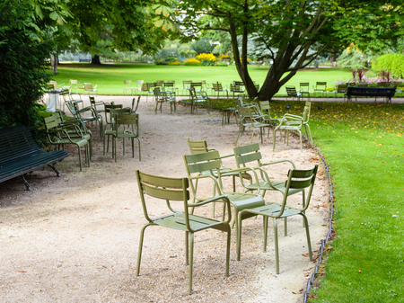 Quiet morning in the Luxembourg garden with typical metallic chairs of the public gardens of Paris scattered along the walkways. Stock Photo