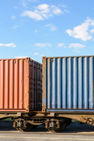 Two containers on a flat car train parked in a shipping yard in the suburbs of Paris, France.