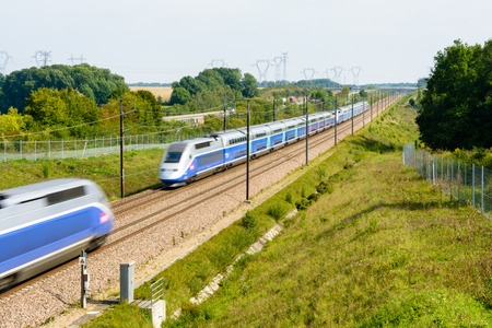 Moisenay, France - August 23, 2017: Two double-decker high-speed TGV Duplex trains crossing on the Paris-Lyon high-speed line in the french countryside.