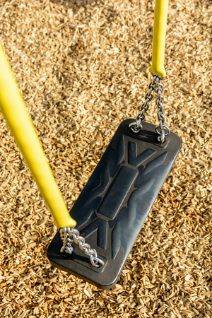 A still childs swing in black plastic in a wood chips covered playground with chrome chains in a yellow plastic sleeve. Stock Photo