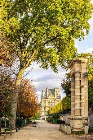 View of the Tuileries garden in Paris at the end of an autumn day with a remnant arch of the Tuileries palace in the foreground and the Flore pavilion in the background.
