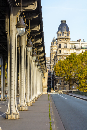 Alignment of metal pillars supporting the subway track of the Bir-Hakeim bridge in Paris and an Haussmannian style building with a raised dome in the background. Stock Photo