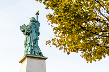 Rear view from below of the replica of the Statue of Liberty in Paris with yellow leaves in the foreground.