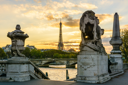 The Eiffel Tower at sunset seen from the Alexander III bridge with a Lion sculpture by Georges Gardet in the foreground. Stock Photo