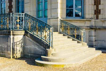Sceaux, France - November 26, 2017: The garden side staircase of the Sceaux castle  with its wrought iron railing, by a sunny morning. Editorial