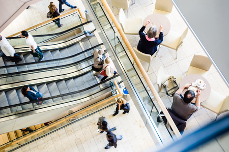 Typical scene in a shopping center : people of various sexes and ages strolling along the walkways, taking the escalators and having a snack at the table. Stock Photo