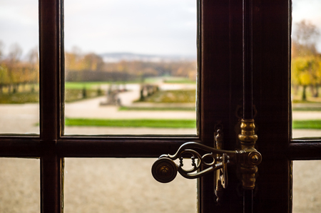 Close-up view of an espagnolette type locking device on a wooden casement window in a french castle with a blurry landscape background showing a french formal garden. Stock Photo