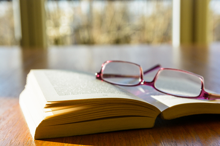 Close-up view of an open pocket book with a pair of reading glasses on it, laying flat on a wooden table and illuminated by a ray of sunlight, in front of a window.
