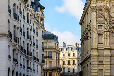 Typical parisian residential buildings of Haussmannian and Art Deco style in chic neighborhoods of the city at sunset.
