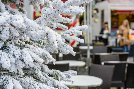 a traditional christmas tree covered with fake snow in front of an empty cafe terrace with