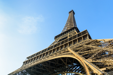 Dynamic view from below of the Eiffel Tower against blue sky.