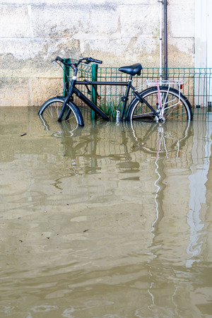 A bicycle attached with a U-lock to a grid on the riverbanks of the Seine with water at mid-height after the swollen river bursts its banks during a winter flood.