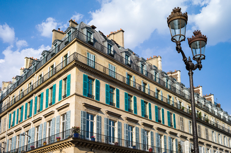 A typical Haussmannian building in Paris with balconies and shutters and a street light in the foreground under a warm light of late afternoon.