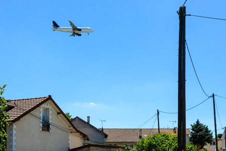 An airliner in landing approach flying above a residential area with houses in the foreground.