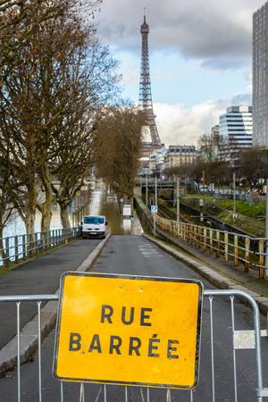 The road going down to the Grenelle port, along the RER C railway, is closed by a safety barrier after the Seine flooded the wharfs during a winter flooding episode. Stock Photo