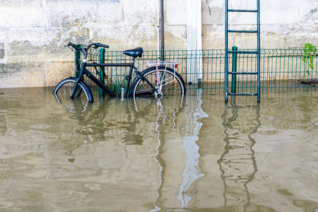 A bicycle attached with a U-lock to a grid, next to a metallic escape ladder, on the riverbanks of the Seine with water at mid-height after the swollen river bursts its banks during a winter flood. Stock Photo