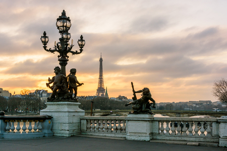 View of the Eiffel tower from the Pont Alexandre III at sunset with one of its Art Nouveau street lamp, ornamented with cherubs, in the foreground.