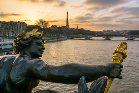View from behind of one of the Nymphs of the Seine ornamenting the downstream keystone of the Pont Alexandre III, with the Pont des Invalides and the Eiffel tower in the background at sunset. Stock Photo