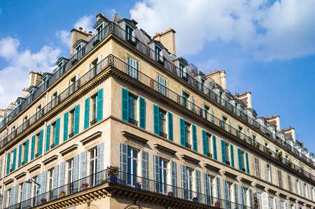 A typical Haussmannian building in Paris with balconies and shutters under a warm light of late afternoon.