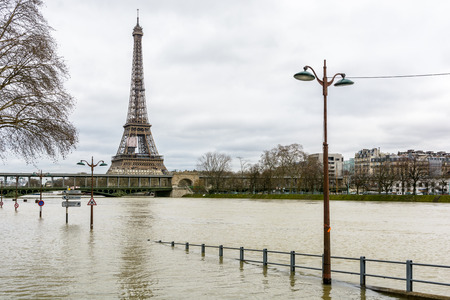 View of the swollen Seine during the winter flooding episode of January 2018, with the flooded expressway in the foreground and the Eiffel tower and Bir-Hakeim bridge in the background.