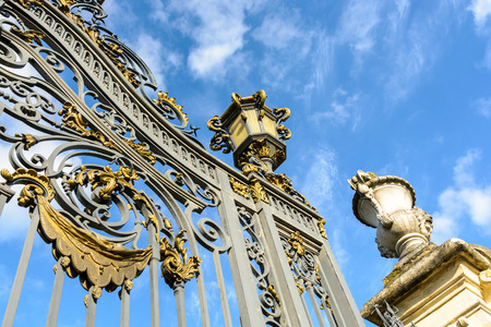 Low angle view of the richly decorated main entrance gate of the Noisiel public park, in the eastern suburbs of Paris, with golden wrought iron leaves, lantern and carved stone vase against blue sky. Stock Photo